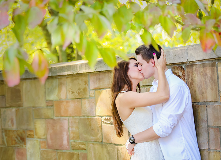 Engaged couple sharing kiss by stone wall