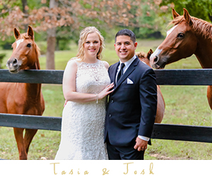 Bride and groom standing by horses rustic